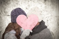 A Composite image of couple in warm clothing holding heart Royalty Free Stock Photography