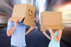 Composite image of couple wearing emoticon face boxes on their heads. Couple wearing emoticon face boxes on their heads against blurry new york street Royalty Free Stock Photos
