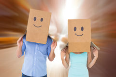 Composite image of couple wearing emoticon face boxes on their heads. Couple wearing emoticon face boxes on their heads against blurry new york street Royalty Free Stock Images