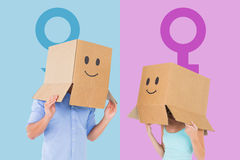 Composite image of couple wearing emoticon face boxes on their heads Stock Image