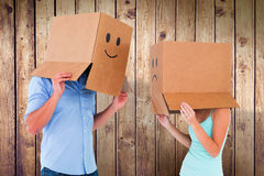 Composite image of couple wearing emoticon face boxes on their heads Stock Photos