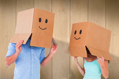 Composite image of couple wearing emoticon face boxes on their heads Royalty Free Stock Image