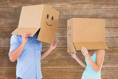Composite image of couple wearing emoticon face boxes on their heads Stock Images