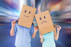 Composite image of couple wearing sad face boxes on their heads. Couple wearing sad face boxes on their heads against blurry new york street Stock Photo