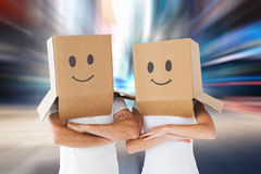 Composite image of couple wearing smiley face boxes on their heads Royalty Free Stock Photo