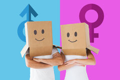 Composite image of couple wearing smiley face boxes on their heads Stock Images
