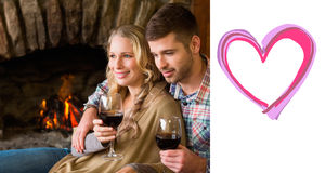 Composite image of couple with wineglasses in front of lit fireplace. Couple with wineglasses in front of lit fireplace against heart Royalty Free Stock Photos