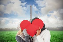 Composite image of couple in winter fashion posing with heart shape Stock Image