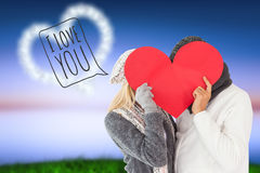 Composite image of couple in winter fashion posing with heart shape Royalty Free Stock Photos