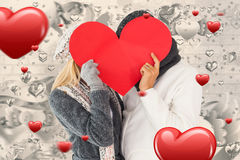 Composite image of couple in winter fashion posing with heart shape. Couple in winter fashion posing with heart shape against grey valentines heart pattern royalty free stock photo
