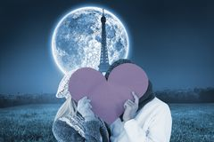 Composite image of couple in winter fashion posing with heart shape Royalty Free Stock Image