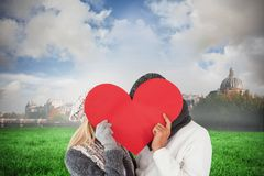 Composite image of couple in winter fashion posing with heart shape Stock Photography