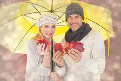 Composite image of couple in winter fashion showing autumn leaves under umbrella Stock Image