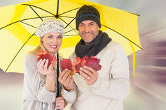 Composite image of couple in winter fashion showing autumn leaves under umbrella Stock Photos