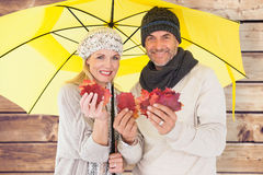 Composite image of couple in winter fashion showing autumn leaves under umbrella Royalty Free Stock Image