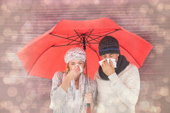 Composite image of couple in winter fashion sneezing under umbrella. Couple in winter fashion sneezing under umbrella against light glowing dots design pattern stock images