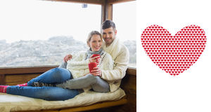 Composite image of couple in winter wear with coffee cups against cabin window Royalty Free Stock Image