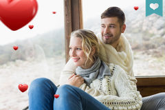 Composite image of couple in winter wear looking out through cabin window Royalty Free Stock Photography