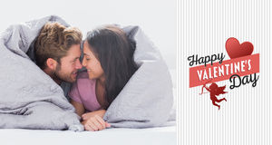 Composite image of couple wrapped in the duvet Royalty Free Stock Photography