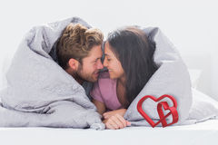 Composite image of couple wrapped in the duvet Royalty Free Stock Photo