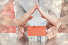 Composite image of couples hands with model house Stock Photography