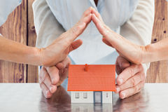 Composite image of couples hands with model house Stock Photo