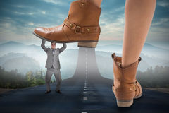 Composite image of cowboy boots stepping on businessman Royalty Free Stock Image