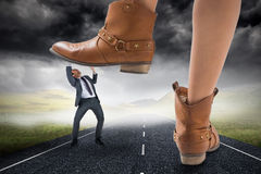 Composite image of cowboy boots stepping on businessman Stock Photo