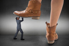 Composite image of cowboy boots stepping on businessman Stock Photos