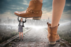 Composite image of cowboy boots stepping on businesswoman Royalty Free Stock Image