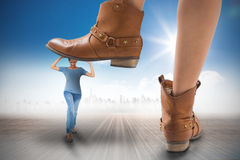 Composite image of cowboy boots stepping on girl Royalty Free Stock Photography