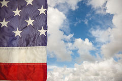 Composite image of creased us flag. Creased US flag against blue sky with white clouds Stock Photos
