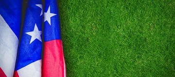 Composite image of creased us flag. Creased US flag against closed up view of grass royalty free stock photography
