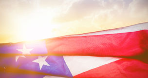 Composite image of creased us flag. Creased US flag against sunset with clouds stock photography