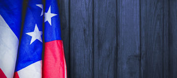 Composite image of creased us flag. Creased US flag against wood Royalty Free Stock Images