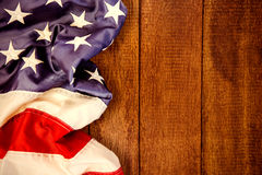 Composite image of creased us flag. Creased US flag against wooden background stock images