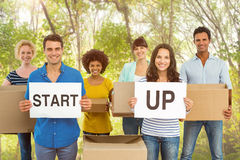 Composite image of creative business team holding cardboard written start up Stock Photos