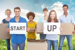 Composite image of creative business team holding cardboard written start up Stock Photography