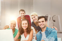 Composite image of creative business team using laptop in meeting Stock Images
