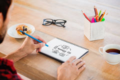 Composite image of creative businessman writing notes on notebook Royalty Free Stock Photos