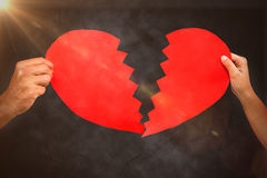 Composite image of cropped couple hands holding red cracked heart shape Royalty Free Stock Images