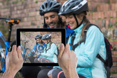 Composite image of cropped hand holding digital tablet. Cropped hand holding digital tablet against biker couple using mobile phone Royalty Free Stock Photos