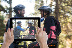 Composite image of cropped hand holding digital tablet. Cropped hand holding digital tablet against men adjusting bicycle helmet of woman Stock Photography