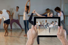 Composite image of cropped hand holding digital tablet. Cropped hand holding digital tablet against side view of women performing stretching exercise Royalty Free Stock Photo