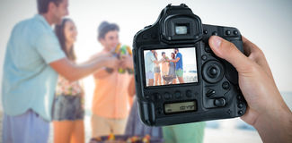 Composite image of cropped hand of photographer holding camera. Cropped hand of photographer holding camera  against happy friends by barbecue holding beer Royalty Free Stock Image