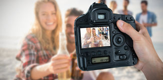 Composite image of cropped hand of photographer holding camera. Cropped hand of photographer holding camera  against happy friends having fun around barbecue Stock Image
