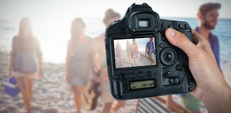 Composite image of cropped hand of photographer holding camera. Cropped hand of photographer holding camera  against happy friends having fun together Royalty Free Stock Photo