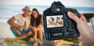 Composite image of cropped hand of photographer holding camera. Cropped hand of photographer holding camera  against portrait of cheerful friends having barbecue Stock Photography