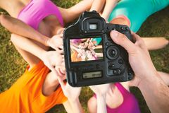 Composite image of cropped hand of photographer holding camera. Cropped hand of photographer holding camera against beautiful young women lying on grass Stock Photography