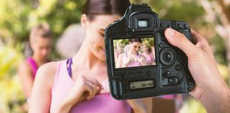 Composite image of cropped hand of photographer holding camera. Cropped hand of photographer holding camera against female volunteer putting ribbon on tank top Stock Photos